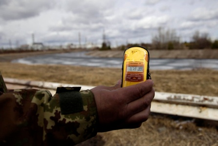 A tour guide measures radiation at the site of Chernobyl.